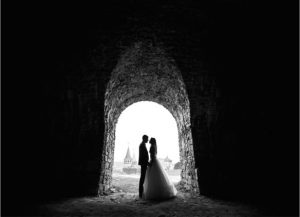 Wedding photography, couple under arch in black and white
